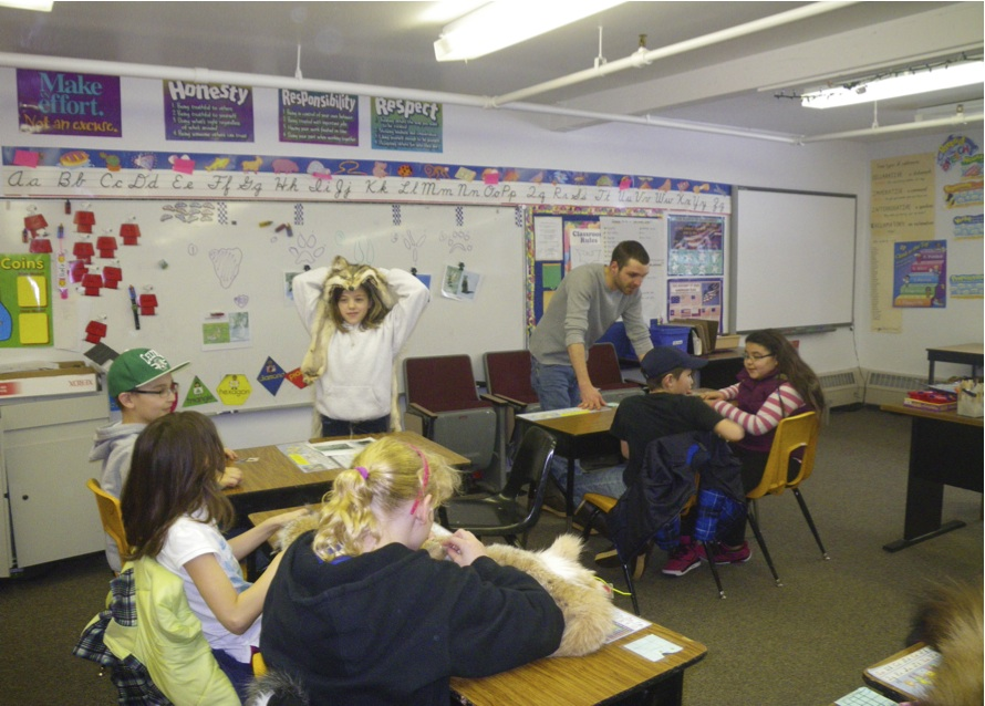 Americorps member Phillip Carson shows animal hides to 4th & 5th graders studying animal tracks